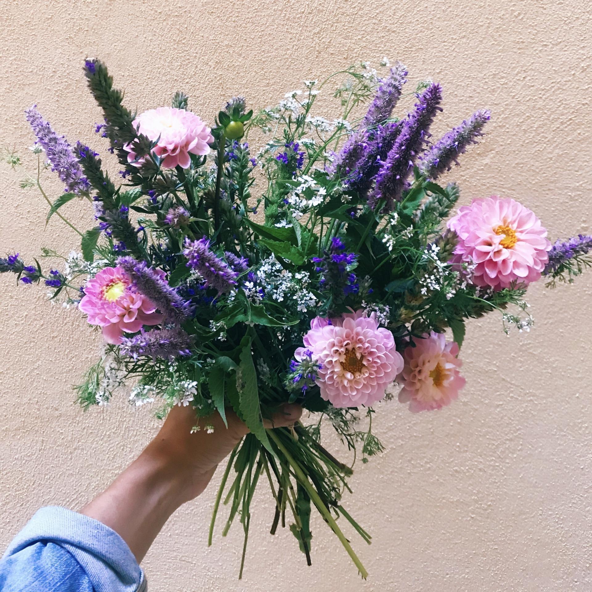 Anaïs, fleuriste à Lyon est de dos tirant un chariot rempli de fleurs locales et de fleurs comestibles qu'elle a cueilli elle-même.